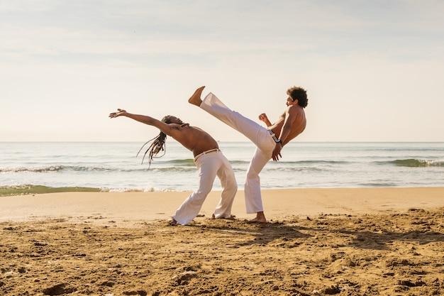 Uomini che addestrano capoeira sulla spiaggia Foto Premium