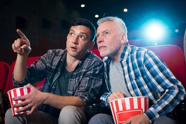 Uomini che guardano film al cinema Foto Gratuite