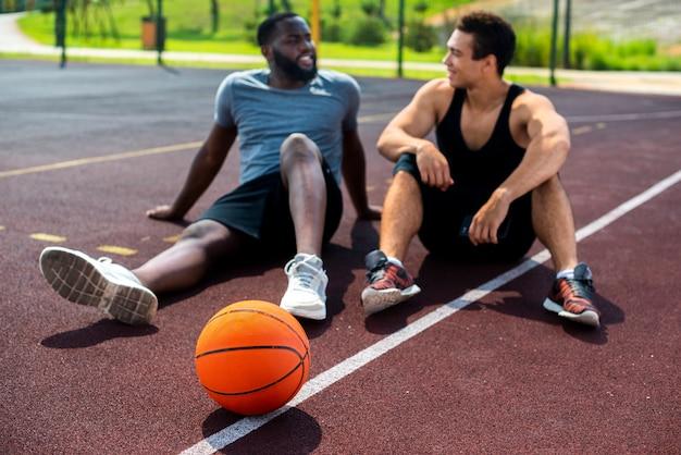 Uomini che parlano sul campo da basket Foto Gratuite