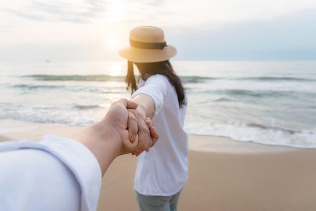 Uomini che si tengono per mano le donne sulla spiaggia per essere felici Foto Premium