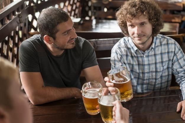 Uomini con alcolici che riposano al tavolo da bar Foto Gratuite