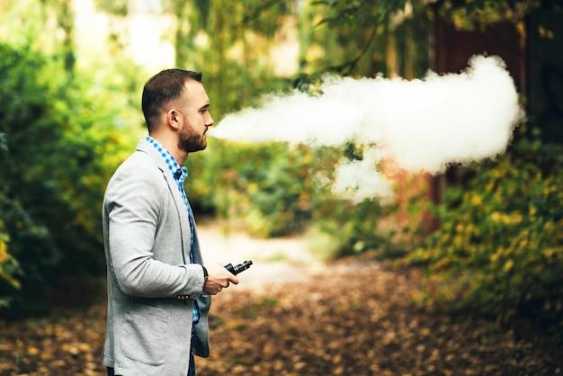 Uomini con la barba che fuma sigaretta elettronica all'aperto Foto Premium