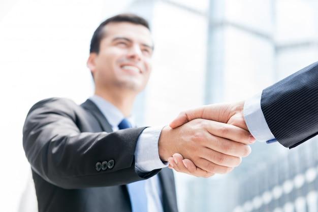 Uomini d'affari che fanno stretta di mano davanti agli edifici per uffici nella città Foto Premium