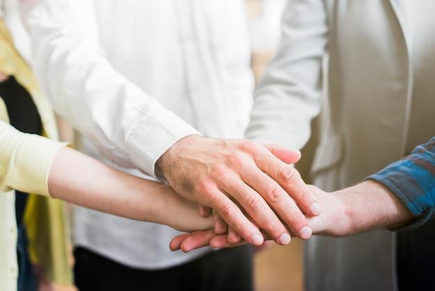 Uomini d'affari che impilano le loro mani per mostrare l'unità Foto Gratuite