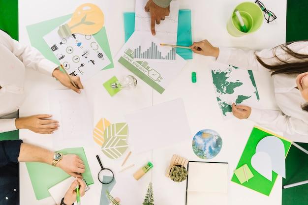 Uomini d'affari che lavorano sul grafico con varie icone delle risorse naturali sulla scrivania Foto Gratuite