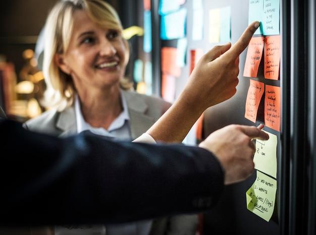 Uomini d'affari che progettano le attività con le note appiccicose Foto Gratuite