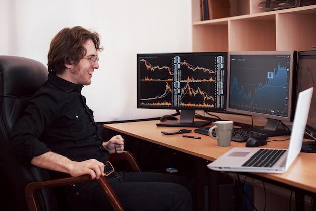 Uomini d'affari che scambiano titoli online. agente di cambio guardando grafici, indici e numeri su schermi di più computer. concetto di successo aziendale Foto Premium