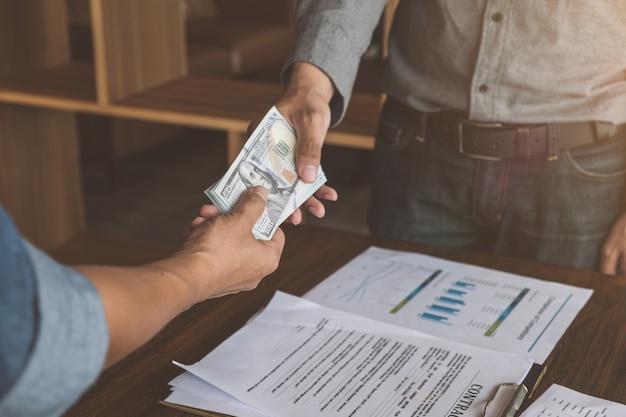 Uomini d'affari che stringono la mano con soldi in mani, corruzione e concetti di corruzione. Foto Premium
