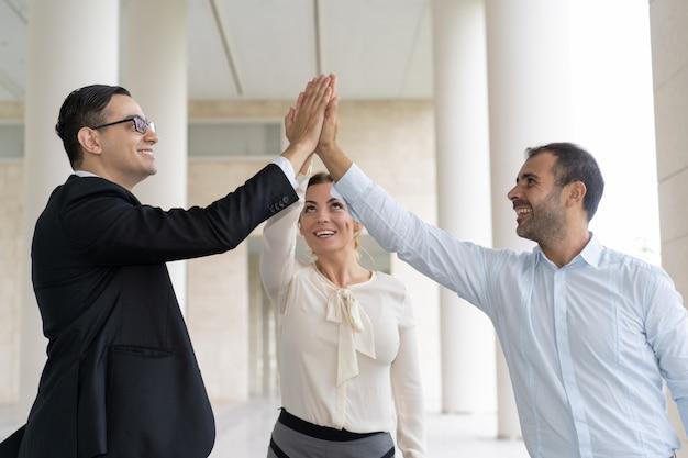 Uomini d'affari gioiosi dando il cinque per celebrare il successo Foto Gratuite