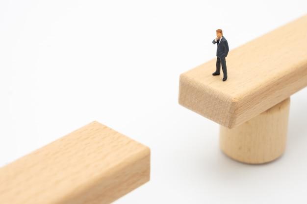 Uomini d'affari in miniatura della gente che stanno su un ponte di legno che guarda Foto Premium