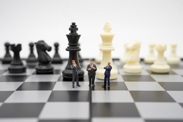 Uomini d'affari in miniatura della gente che stanno su una scacchiera con un pezzo degli scacchi sopra Foto Premium