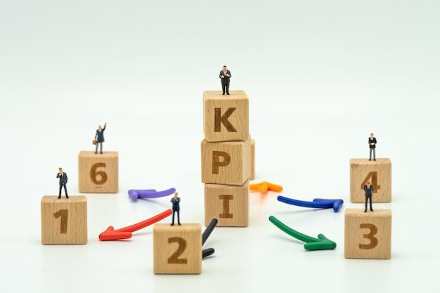 Uomini d'affari in miniatura della gente che stanno sulla parola di legno kpi personnel kpi Foto Premium