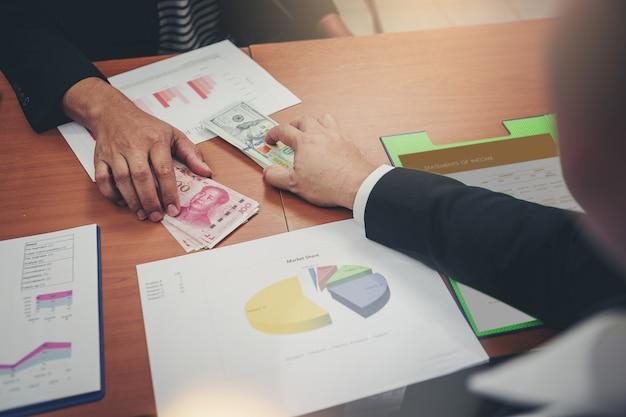 Uomini d'affari in possesso di dollari usd, yuan rmb per la condivisione di denaro per investimenti in cambi. guerra commerciale Foto Premium