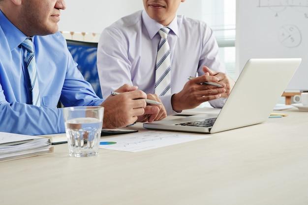 Uomini d'affari potati che discutono cooperazione ad una riunione con bicchiere d'acqua, documenti e computer portatile sul desktop Foto Gratuite
