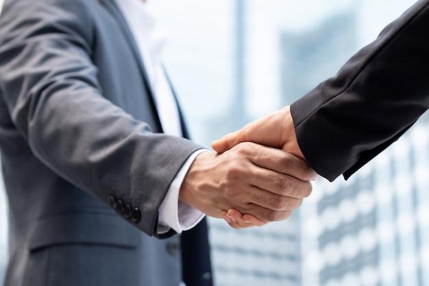 Uomini d'affari rendendo stretta di mano in città Foto Premium