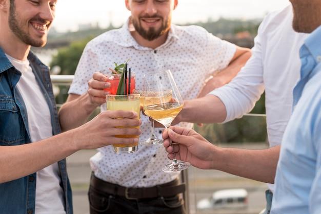 Uomini del primo piano che tostano ad una festa Foto Gratuite