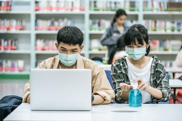 Uomini e donne indossano maschere e usano un computer portatile per cercare libri in biblioteca. Foto Gratuite