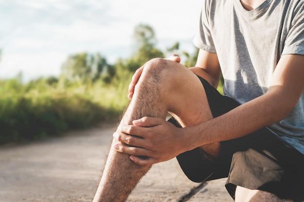 Uomini feriti dall'esercizio fisico, usa le mani per tenere le ginocchia al parco Foto Premium