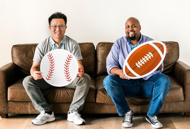 Uomini in possesso di icone di baseball e rugby seduto sul divano Foto Premium