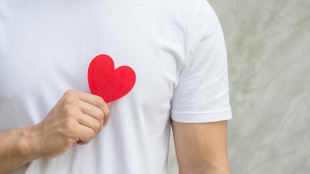 Uomini in possesso di un cuore di tessuto rosso su uno sfondo grigio. Foto Premium