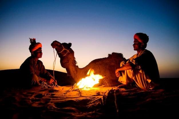 Uomini indiani che riposano accanto al falò con il loro cammello Foto Gratuite