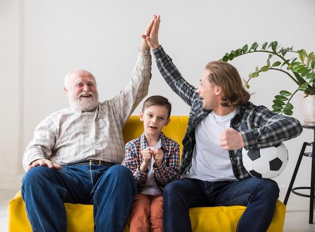 Uomini multigenerazionali che esultano la squadra di football americano di vittoria a casa Foto Gratuite