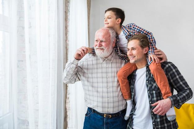 Uomini multigenerazionali in piedi e con il sorriso che distoglie lo sguardo Foto Gratuite