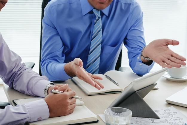 Uomini potati che discutono rapporto annuale facendo uso della compressa digitale Foto Gratuite