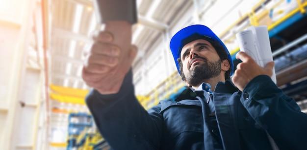 Uomini si stringono la mano in una struttura industriale Foto Premium