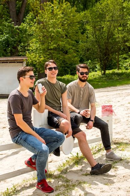 Uomini spensierati godendo bevande sulla spiaggia Foto Gratuite