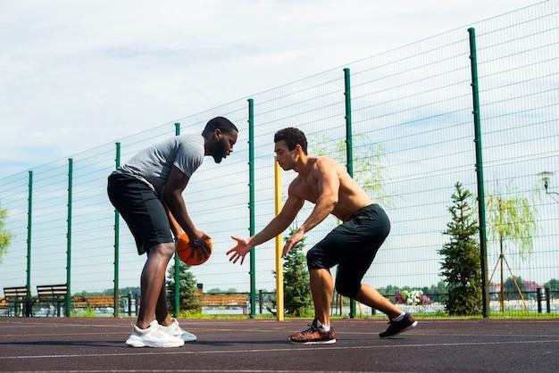 Uomini sportivi che giocano il colpo urbano di angolo basso di pallacanestro Foto Gratuite
