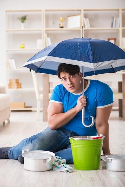 Uomo a casa che si occupa della perdita di inondazione vicina Foto Premium