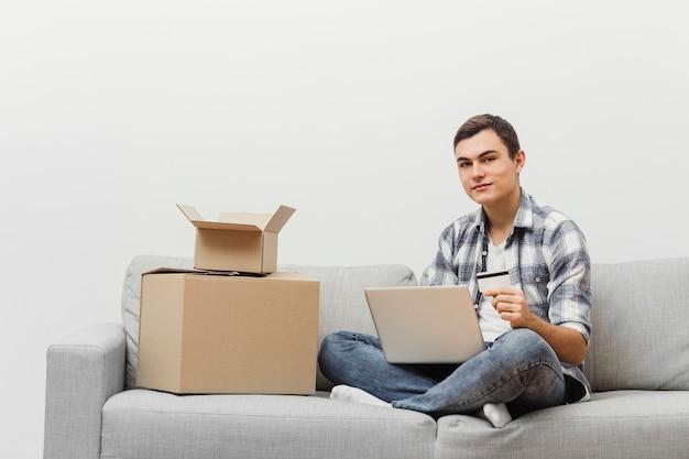 Uomo a casa con scatole da imballaggio Foto Gratuite