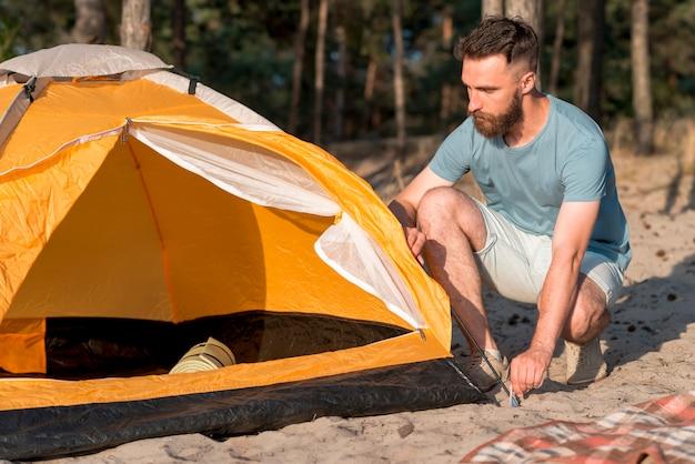 Uomo accovacciato che installa la tenda Foto Gratuite