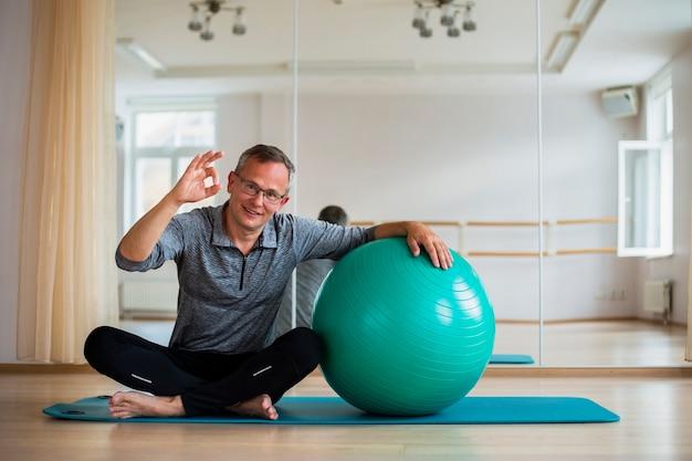 Uomo adulto adatto che sta accanto alla palla di esercizio Foto Gratuite