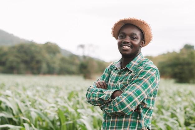Uomo africano agricoltore stand presso la fattoria verde con felice e sorriso. Foto Premium