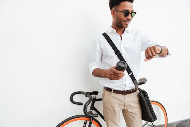 Uomo africano con il caffè bevente della bicicletta. Foto Gratuite