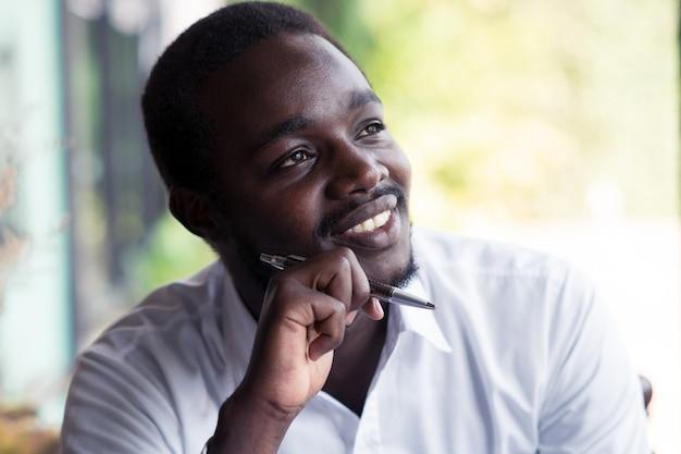 Uomo africano pensando e guardando con in mano una penna. Foto Premium