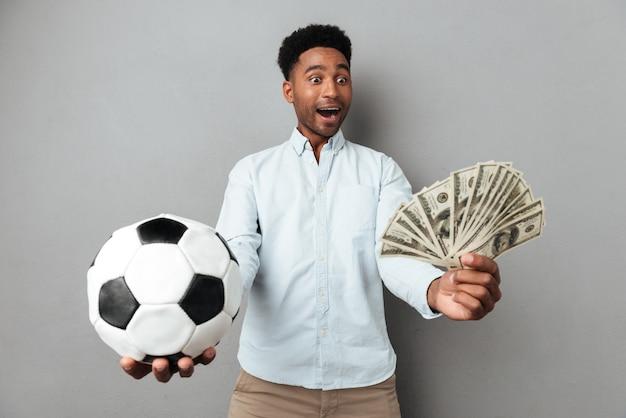 Uomo africano sorridente felice che mostra le banconote dei soldi e di calcio Foto Gratuite