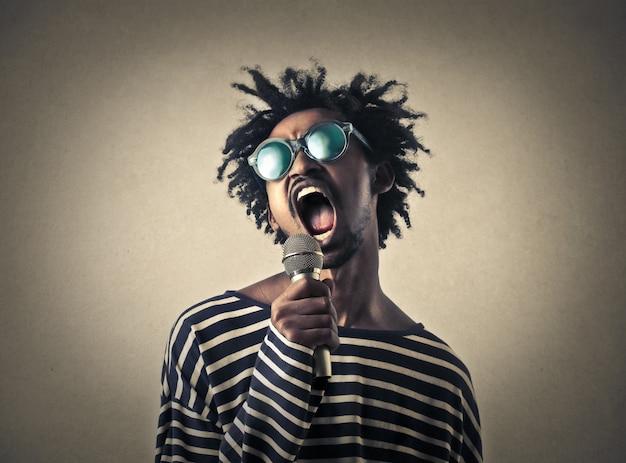 Uomo afro che grida in un microfono Foto Premium