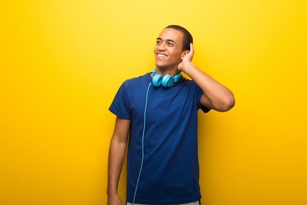 Uomo afroamericano con la maglietta blu su fondo giallo che pensa un'idea mentre graffiando si dirige Foto Premium