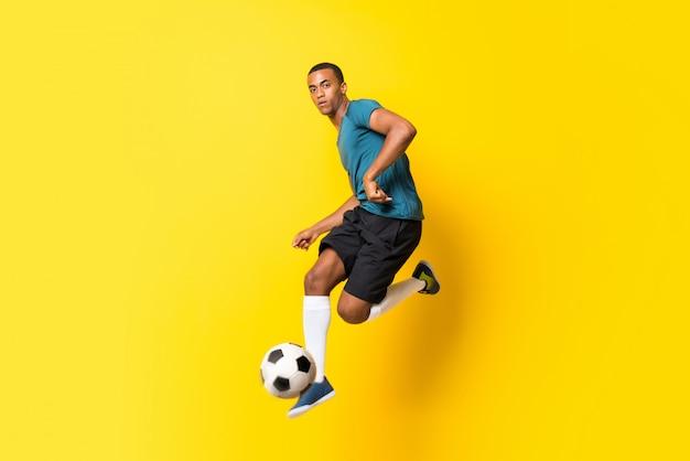 Uomo afroamericano del giocatore di football americano sopra giallo isolato Foto Premium