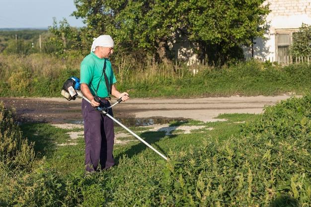 Uomo all'erba di cucito dell'azienda agricola con la falciatrice da giardino Foto Gratuite