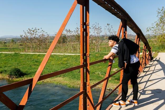 Uomo alla moda bello che sta sul ponte sopra il bello fiume Foto Gratuite