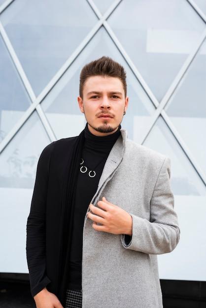 Uomo alla moda che guarda l'obbiettivo Foto Gratuite