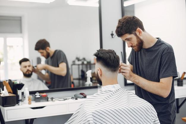 Uomo alla moda che si siede in un barbiere Foto Gratuite