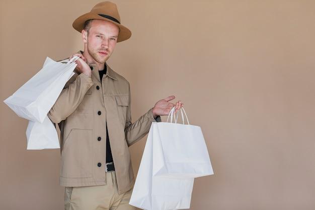 Uomo alla moda con i sacchetti della spesa che guarda alla macchina fotografica Foto Gratuite