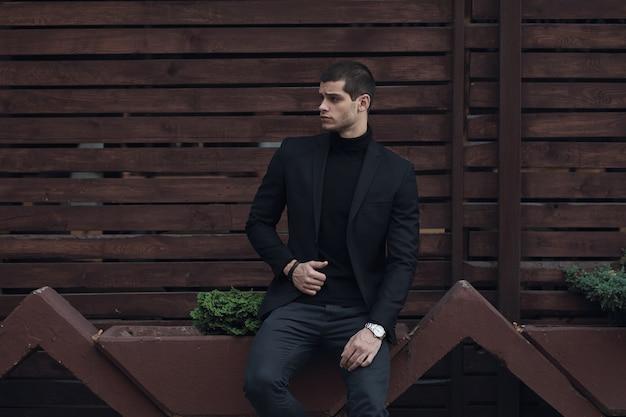 Uomo alla moda, indossa un abito, seduto contro la parete di legno Foto Gratuite