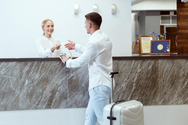 Uomo alla reception dell'hotel. Foto Premium