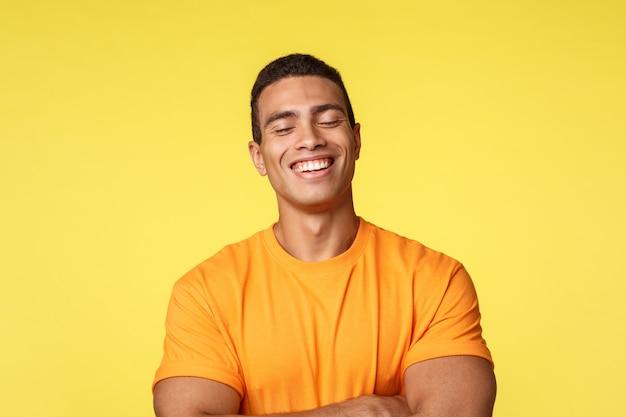 Uomo allegro bello in maglietta, ridendo con gli occhi chiusi Foto Premium